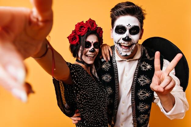 Maravillosa pareja en disfraces de halloween haciendo selfie. dama sonriente en traje mexicano celebrando el día de los muertos con su novio.