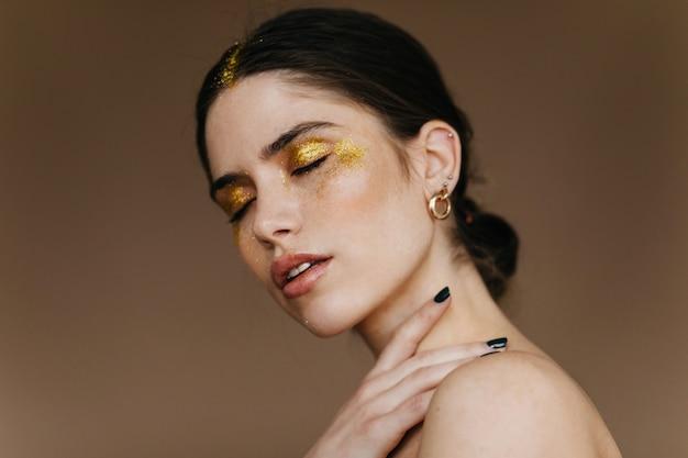 Maravillosa señorita con elegante pendiente de oro posando en la pared oscura. mujer morena extasiada con maquillaje de fiesta de pie con los ojos cerrados.