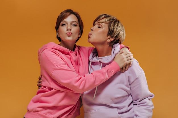 Maravillosas dos mujeres con peinado corto y elegante en modernas sudaderas con capucha rosadas abrazándose y soplando besos sobre fondo naranja.