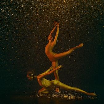 Maravilloso. dos jóvenes bailarinas de ballet bajo gotas de agua y spray. modelos caucásicos y asiáticos bailando juntos en luces de neón. concepto de ballet y coreografía contemporánea. foto de arte creativo.