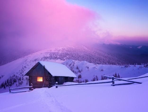 Maravilloso paisaje de invierno con casa de montaña en la nieve