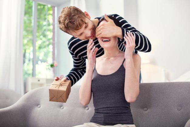 Maravilloso regalo. feliz mujer emocionada sonriendo mientras espera un regalo de su novio