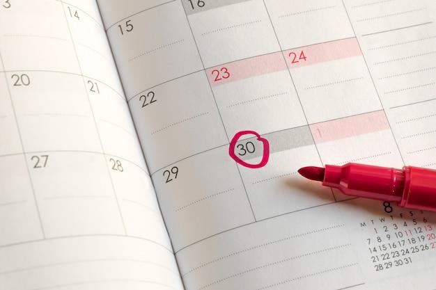 Marca roja en la fecha marcada en un círculo en el calendario mensual