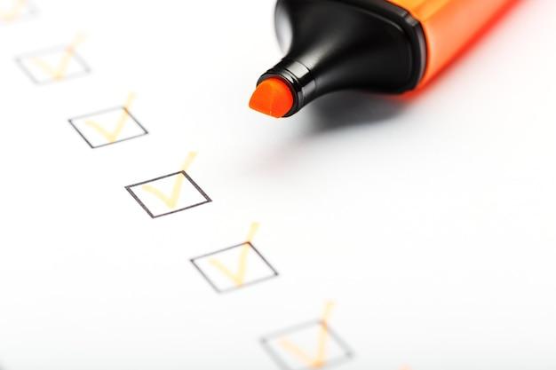 Marcador naranja con marcadores en la hoja de lista de verificación. lista de verificación concepto de tarea completada.