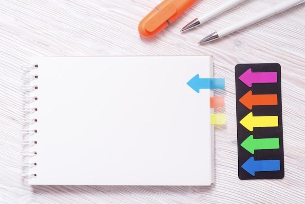 Marcador de página de color, con forma de bultos, sobre escritorio de madera