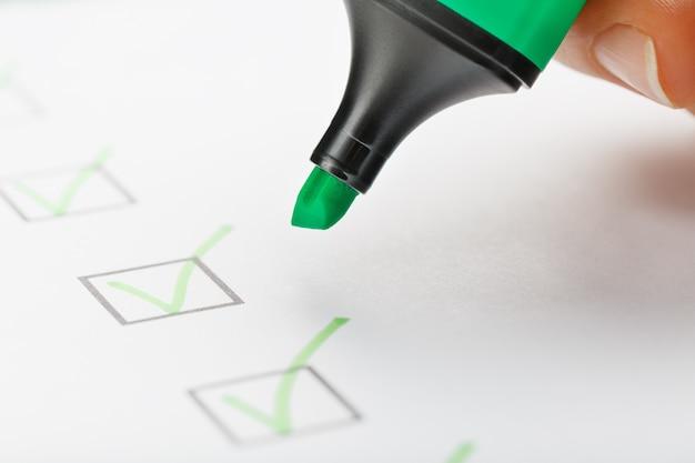 El marcador verde en la hoja de verificación con marcas en forma de garrapatas. conceptos de producción