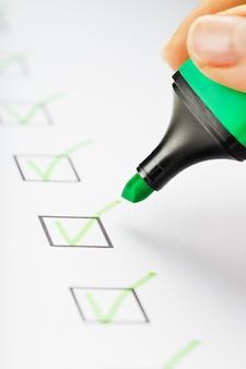 Marcador verde con marcadores en la hoja de lista de verificación. lista de verificación concepto de tarea completada.