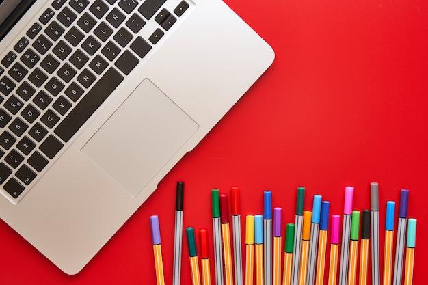 Marcadores coloreados y computadora portátil en un fondo rojo. concepto de regreso a la escuela, diseño y creatividad.