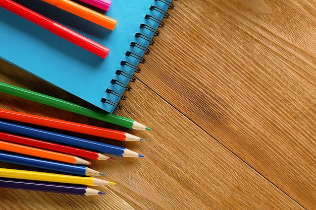 Marcadores de colores, lápices y bloc de notas en una mesa de madera.