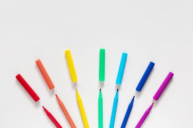 Marcadores de colores sobre superficie blanca