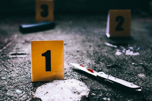 Marcadores de evidencia con cuchillo y cargador de pistola en el suelo