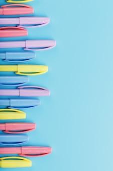 Marcadores multicolores en azul con espacio libre.
