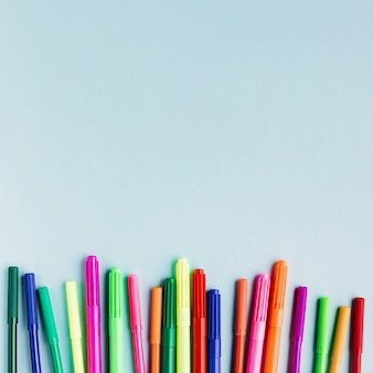 Marcadores multicolores sobre tabla azul