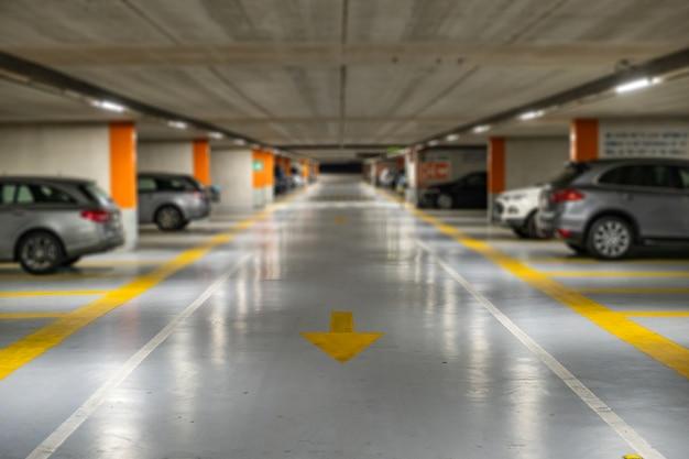 Marcas amarillas con coches modernos borrosos estacionados dentro de un estacionamiento subterráneo cerrado.