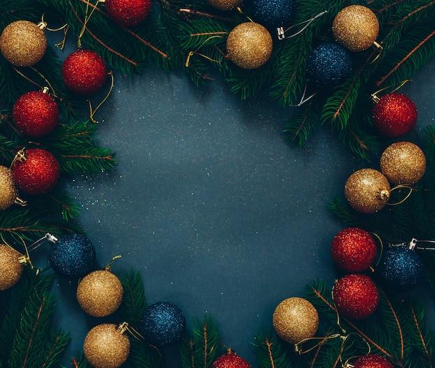 Marco de abeto verde y decoración navideña sobre un fondo negro con espacio vacío