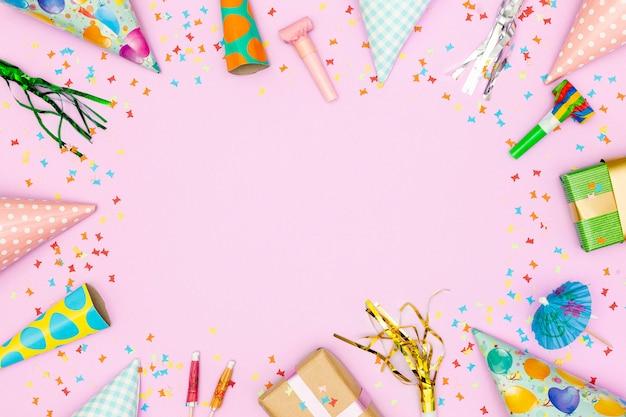 Marco de accesorios de cumpleaños sobre fondo rosa
