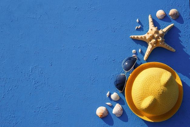 Marco con accesorios de playa en un sombrero de paja amarillo de tema náutico, gafas de sol, estrellas de mar y conchas en azul. endecha plana