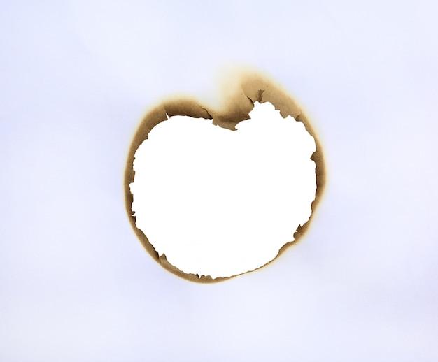 Marco de agujero quemado en papel blanco.