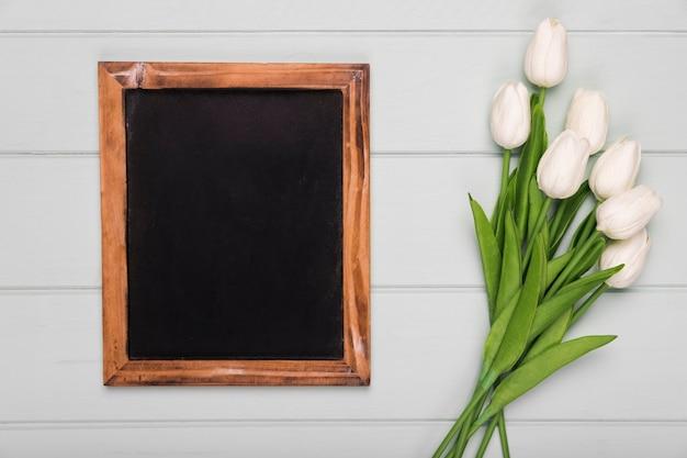 Marco al lado de tulipanes blancos en la mesa