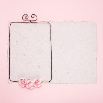 Marco de alambre rectangular decorado con rosas sobre papel sobre fondo rosa