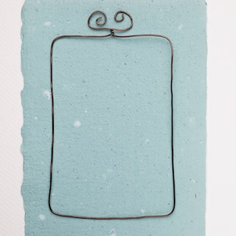 Marco de alambre rectangular sobre papel azul sobre fondo blanco.