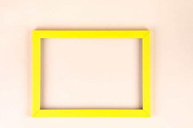 Marco amarillo aislado sobre fondo beige con copyspace, endecha plana