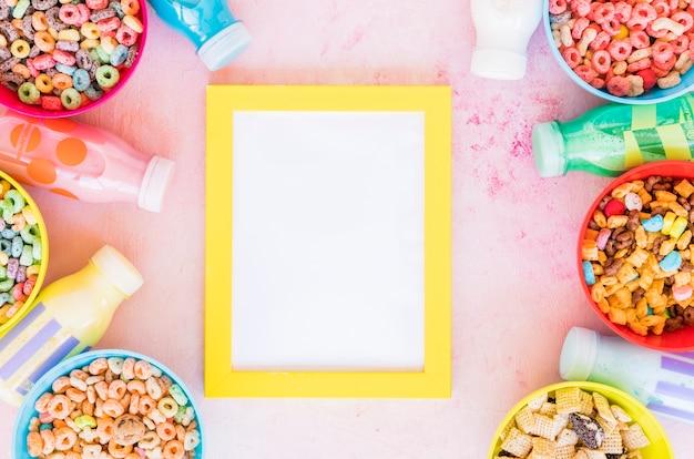 Marco amarillo con cuencos de cereales y leche.