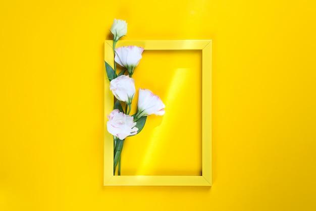 Marco amarillo y flores eustoma con un rayo de sol sobre fondo amarillo, copyspace endecha plana