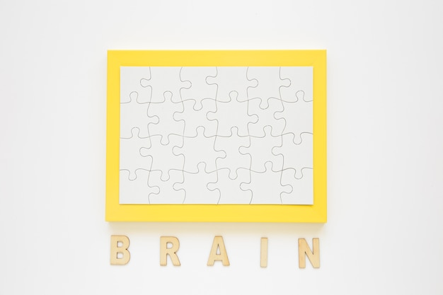 Marco amarillo con rompecabezas cerca de palabra cerebro