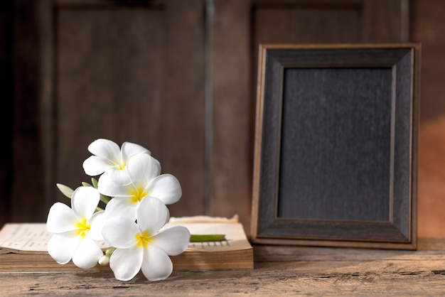 Marco de banco sobre mostrador de madera con flor blanca