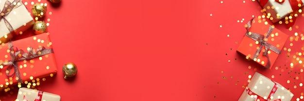 Marco de banner de navidad o año nuevo con cajas de regalo de papel decoradas con cintas de oro brillantes sobre un fondo rojo.