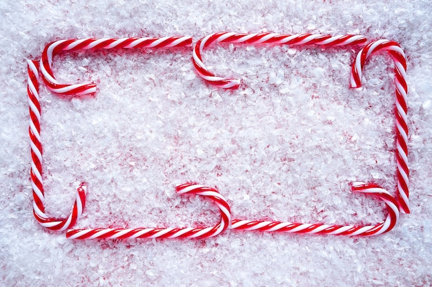 Marco de bastón de caramelo de navidad en la nieve