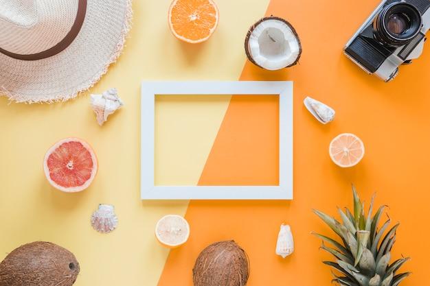 Marco en blanco con accesorios de viaje, frutas y conchas.