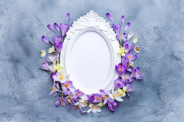 Marco blanco adornado con flores de primavera púrpuras y blancas