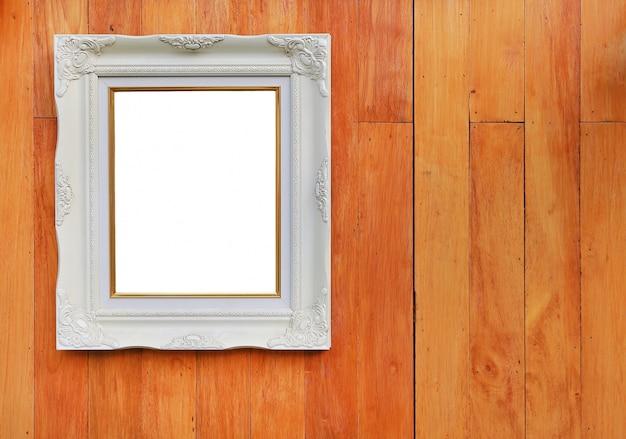 Marco blanco antiguo de la foto con el espacio vacío para su imagen o texto colocado en el fondo de madera de la pared del tablón.