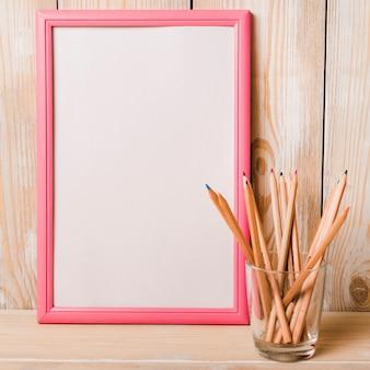Marco blanco en blanco con borde rosa y lápices de colores en el soporte de vidrio en el escritorio de madera