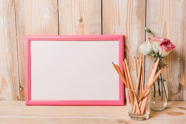 Marco blanco en blanco con borde rosa y lápices de colores en vidrio en escritorio de madera