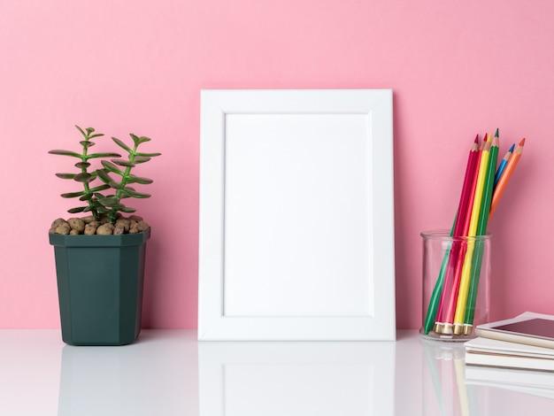 Marco blanco en blanco, crayón en tarro, planta de cactus en mesa blanca contra el rosa