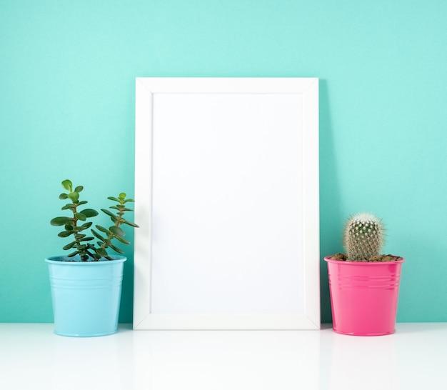 Marco blanco en blanco, planta cactus en mesa blanca contra la pared azul. copia de maqueta