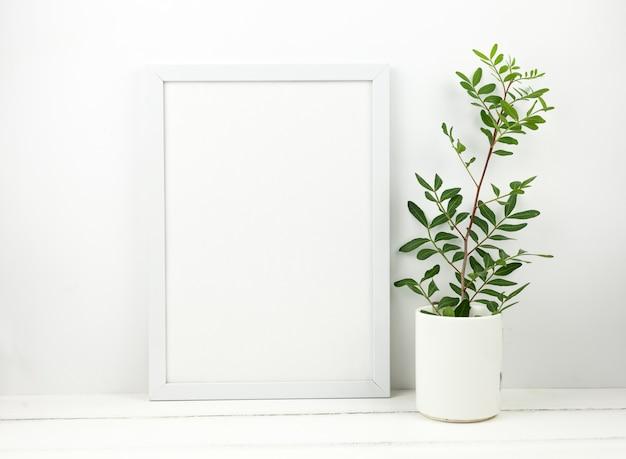 Marco blanco en blanco y planta en maceta en mesa de madera blanca