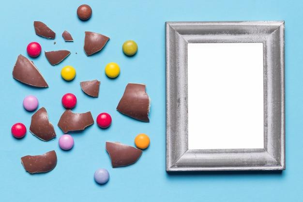 Marco en blanco blanco plateado cerca de las cáscaras de huevo de pascua rotas y caramelos de gema sobre fondo azul