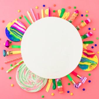 Marco blanco en blanco sobre accesorios de fiesta y dulces en superficie rosa