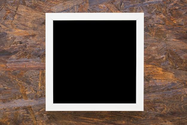 Marco blanco borde negro sobre fondo de madera