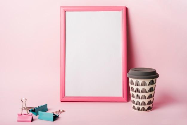 Marco blanco con borde rosa; clips de papel y taza desechable de café sobre fondo rosa