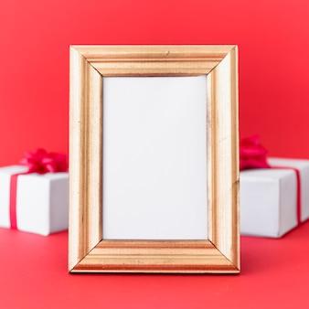 Marco en blanco con cajas de regalo en la mesa