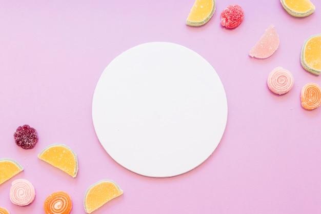 Marco en blanco circular blanco con caramelos de azúcar gelatina en fondo rosa