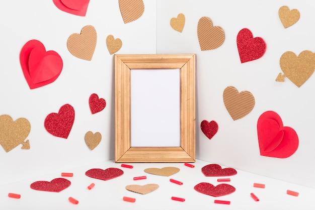 Marco en blanco con corazones de papel en la mesa