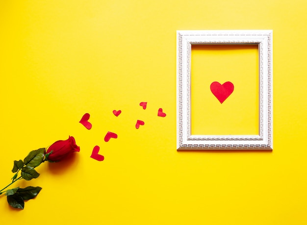 Un marco blanco y corazones sobre un fondo amarillo y una rosa roja espacio para texto