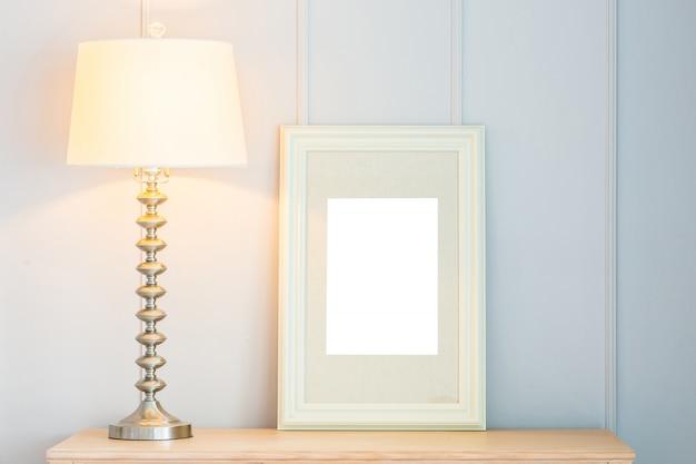 Marco en blanco con decoración de lámpara de luz en mesa
