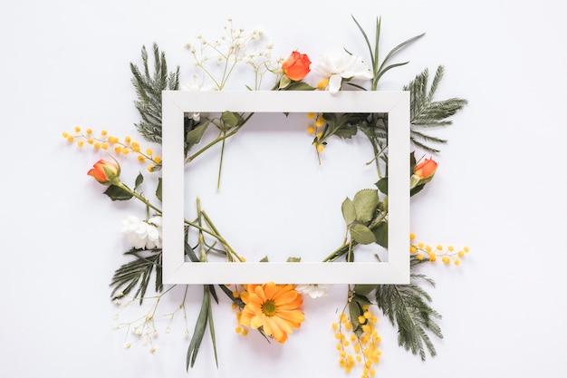 Marco en blanco en diferentes flores en la mesa